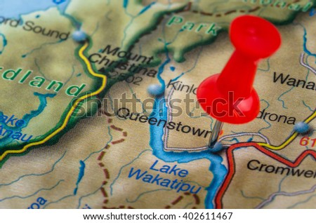 Close/up of a Map of New Zealand with a Red Pushpin Highlighting the City of Queenstown - stock photo