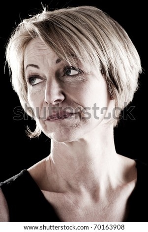 Close-up of a mature actress, black background - stock photo