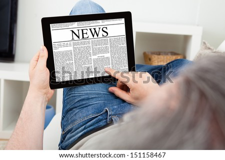 Close-up Of a Mature Man reading news on digital tablet - stock photo