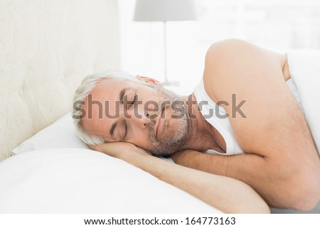 Close-up of a mature man sleeping in bed at home - stock photo