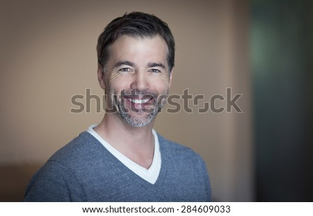 Close-up of a mature man smiling at home - stock photo
