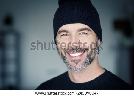 Close Up Of A Mature Man Wearing A Toque Smiling At The Camera - stock photo