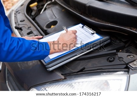 Close-up Of A Mature Mechanic Maintaining Car Records - stock photo