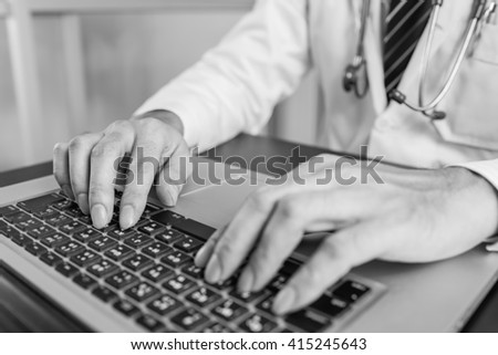 Close-up of a medical worker typing on laptop ,  black and white - stock photo