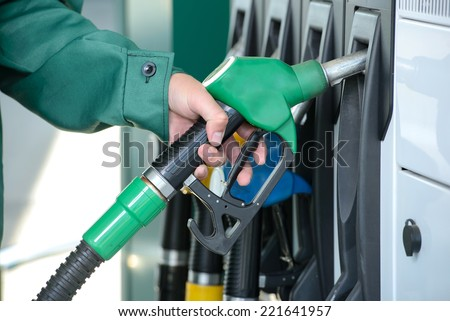 Close-up of a men's hand using a fuel nozzle at a gas station. Petrol station. Filling station. Petrol. Gasoline. - stock photo