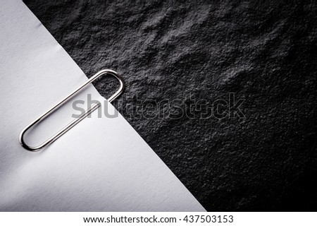 close up of a metal paper clip and paper on black background - stock photo