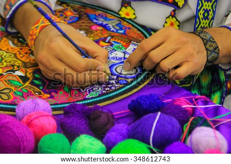 Close up of a Mexican man working of his handcraft with bokeh of yarn in front. - stock photo