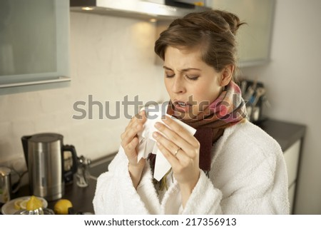 Close-up of a mid adult woman sneezing in the kitchen - stock photo