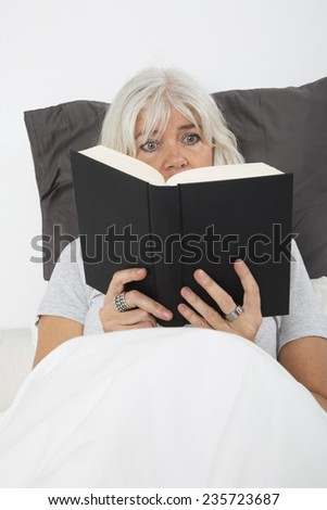 Close up of a Mid age woman reading book in bed, from high angle view - stock photo