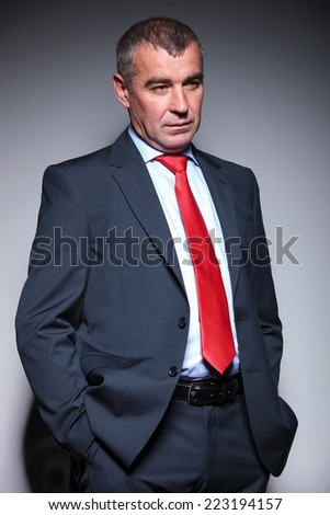Close up of a middle aged business man holding his hands in pocket while looking away from the camera. - stock photo