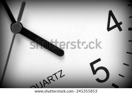 Close up of a modern clock face in black and white with the hour hand pointing at five o'clock. A vignette has been added to the image for effect - stock photo