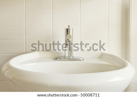 Close-up of a modern stainless steel faucet on an oval, white porcelain pedestal-style sink against a white tile wall. Horizontal format. - stock photo