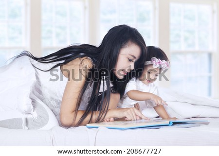 Close-up of a mother and baby girl reading book story on bed - stock photo