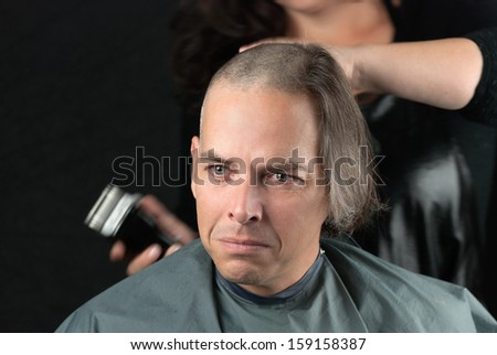 Close-up of a mourning man getting his long hair is shaved off for a cancer fundraiser. - stock photo