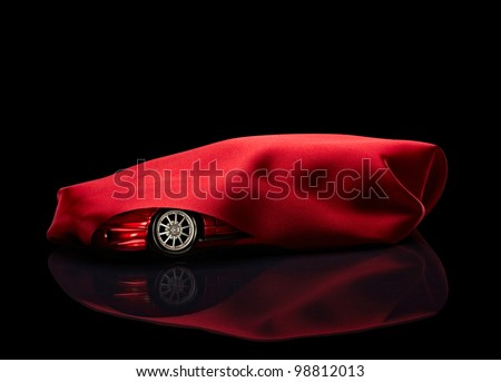 close up of  a new car hidden under red cover on black background with clipping path - stock photo