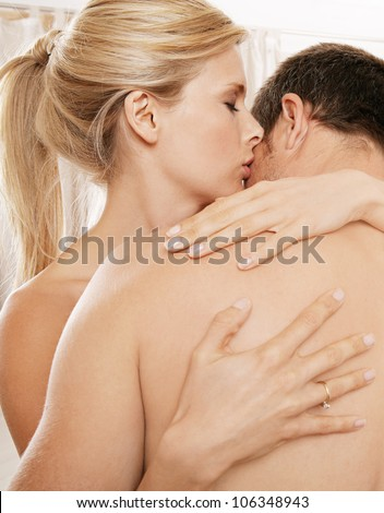 Close up of a nude couple kissing in a bedroom. - stock photo