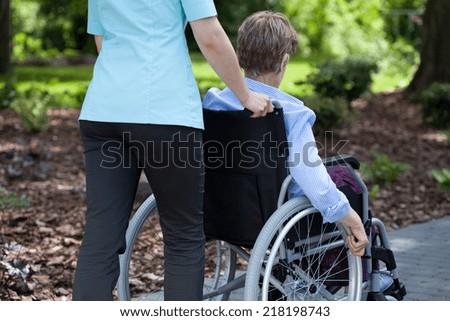 Close-up of a nurse pushing elderly woman on wheelchair - stock photo