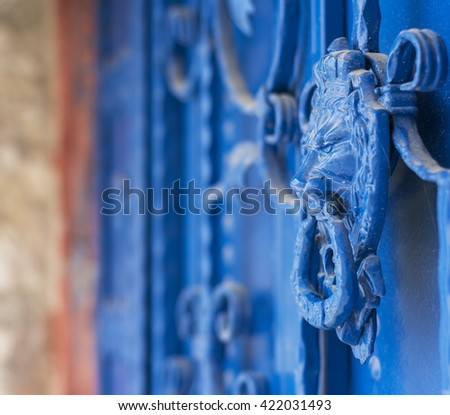 Close-up of a old blue painted wrought iron door  with a lion head shaped door knob  - stock photo