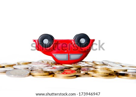 close-up of a overturned red toy car resting on a pile of euro coins on a white background - stock photo