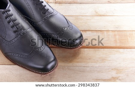 Close up of a pair of leather shoes on top of wooden table - stock photo