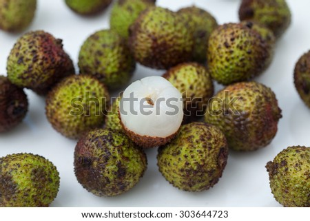 Close up of a peeled lychee with other lychees. - stock photo