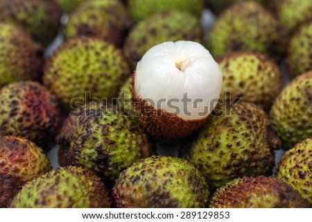 Close up of a peepled lychee with other lychees. - stock photo