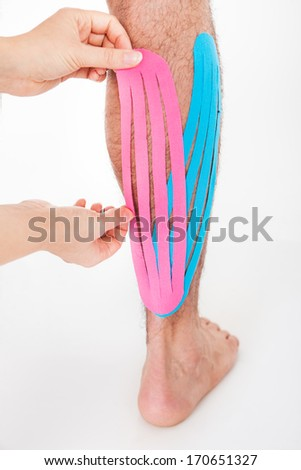 Close-up Of A Person Applying Kinesio Tape On Injured Calf - stock photo