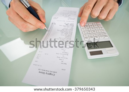 Close-up Of A Person Hand Calculating Shopping Bill - stock photo