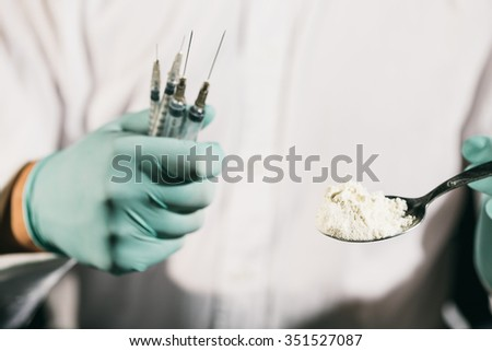 Close-up of a person holding a spoon with cocaine and several syringes  - stock photo