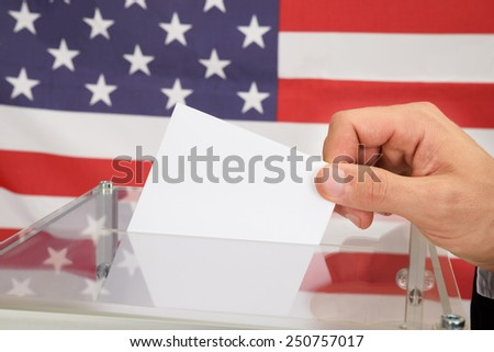 Close-up Of A Person In Front American Flag Putting Ballot In Glass Box - stock photo