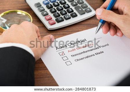 Close-up Of A Person's Hand Filling Audit Checklist Form - stock photo