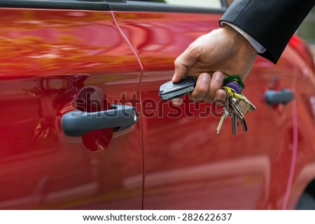 Close-up Of A Person's Hand Holding A Car's Remote Control Pointing To The Door - stock photo