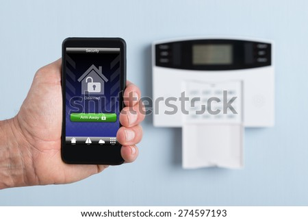 Close-up Of A Person's Hand Holding Remote Control Of Security System. Photographer owns copyright for images on screen - stock photo