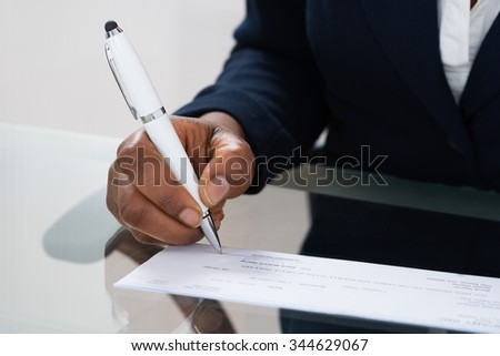 Close-up Of A Person's Hand Signing Cheque - stock photo