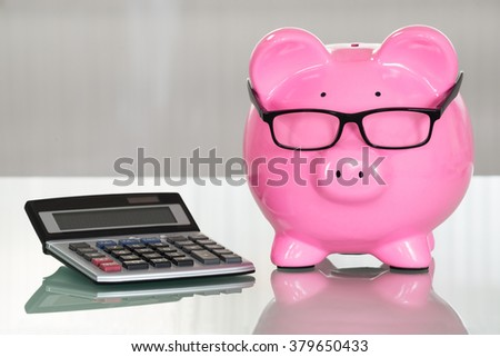 Close-up Of A Piggybank With Eyeglasses And Calculator - stock photo