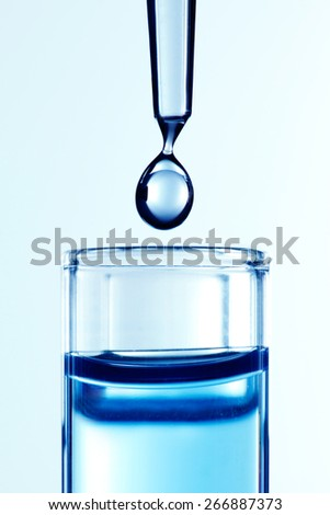 Close up of a pipette dropping a blue sample into a test tube - stock photo