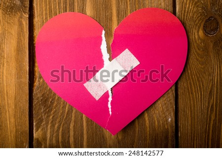 close up of a plaster and paper broken heart on wooden background - stock photo