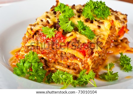Close up of a plate with lasagne - stock photo