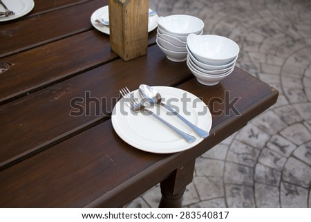 Close up of a plate with spoon and fork on a wooden table - stock photo
