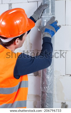 Close-up of a plumber working at construction site - stock photo