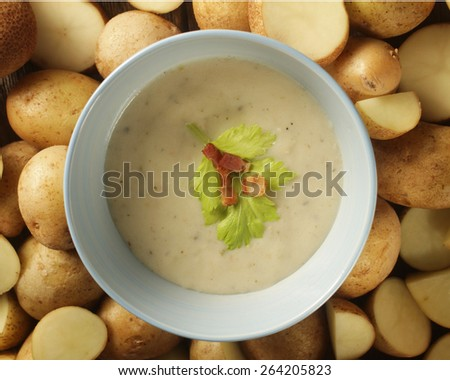 Close up of a potato soup in a pale blue bowl surrounded by potatoes - stock photo