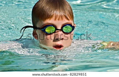 Close up of a preteen boy swimming.  The waves and splashes in the pool are reflected in the goggles. - stock photo