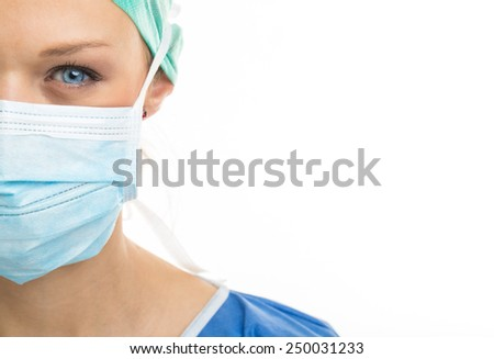 Close up of a pretty, blue-eyed, female surgeon. Half face composition. Looking confident and professional - stock photo