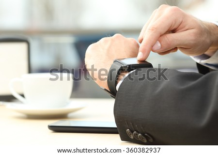 Close up of a professional businessman hands selecting with the finger in a modern generic smart watch on line in table of a coffee shop - stock photo