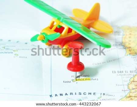 Close-up of a red pushpin on a map of Madeira island and airplane toy- travel concept - stock photo