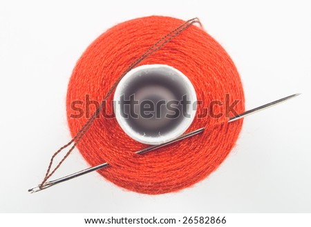 close up of a red sewing spool with a needle - stock photo