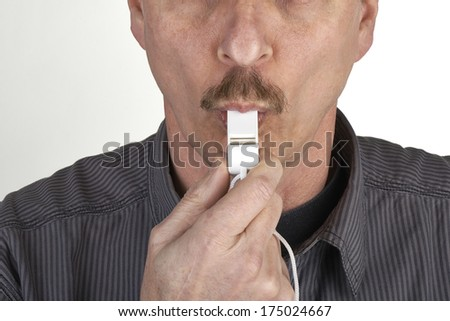 Close up of a referee blowing a whistle - stock photo