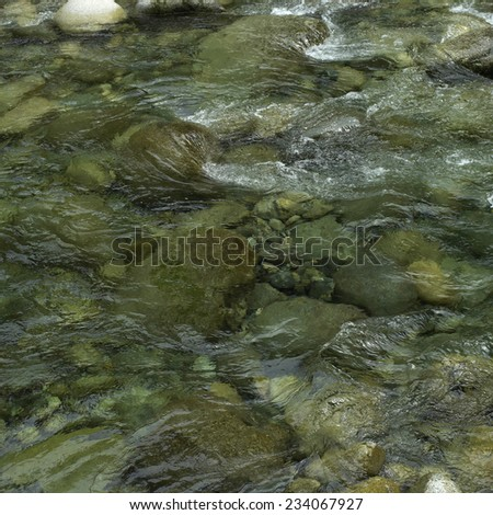 Close up of a river with clear water and stones - stock photo