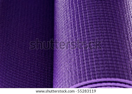 close up of a rolled up yoga or pilates exercise mat isolated on white. - stock photo