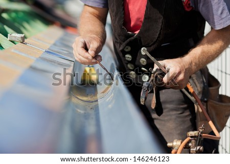 Close-up of a roofer welding the gutter on a new roof - stock photo